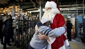 Domore Walker, 14, left, a student at West Caldwell Tech, gives a hug to a man wearing a Santa Claus suit before riding on a New Jersey Transit train at the Hoboken Terminal, Friday, Dec. 1, 2017, in Hoboken, N.J. Schoolchildren were picked up by the train at various stations as part of the agency's annual Railmen For Children Santa Train. (AP Photo/Julio Cortez)