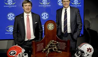 Georgia head coach Kirby Smart, left, and Auburn head coach Gus Malzahn pose with the SEC championship trophy during an NCAA college football news conference in Atlanta, Friday, Dec. 1, 2017. (AP Photo/David Goldman)