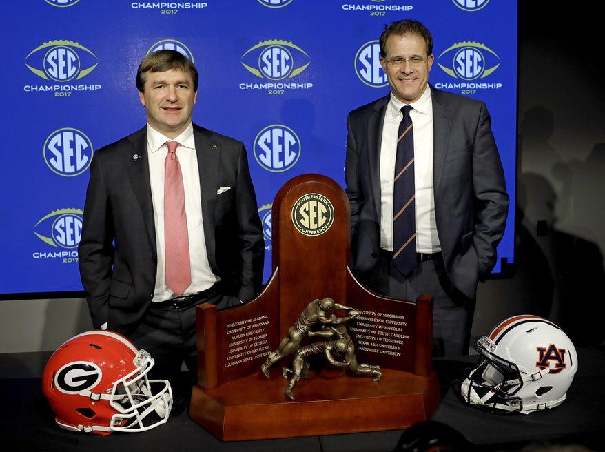 Georgia head coach Kirby Smart, left, and Auburn head coach Gus Malzahn pose with the SEC championship trophy during an NCAA college football news conference in Atlanta, Friday, Dec. 1, 2017. (AP Photo/David Goldman)