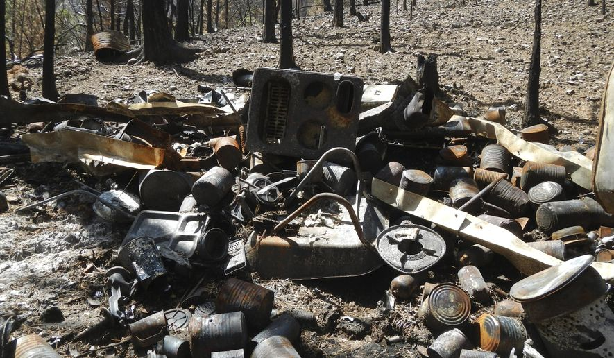 This undated photo provided by the Iron County Sheriff's Office shows the remnants of one of several burned out cabins built a Utah survivalist in the wilderness outside the ski resort town of Brian Head, Utah. The man's stockpiles of guns, grenades and food were discovered when a wildfire burned through the area this summer. (Iron County Sheriff's Office via AP)