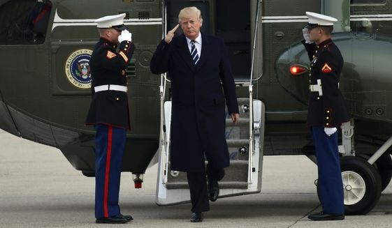 President Donald Trump salutes as he steps off of Marine One and walks towards Air Force One at John F. Kennedy International Airport in New York, Saturday, Dec. 2, 2017. Trump spent the day in New York attending a trio of fundraisers. (AP Photo/Susan Walsh)