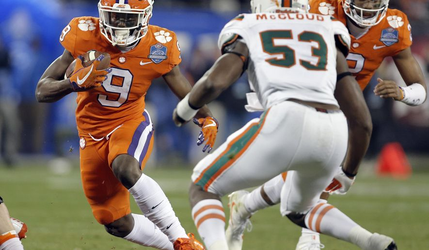 Clemson's Travis Etienne (9) runs against Miami's Zach McCloud (53) during the first half of the Atlantic Coast Conference championship NCAA college football game in Charlotte, N.C., Saturday, Dec. 2, 2017. (AP Photo/Bob Leverone)