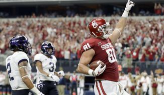 Oklahoma tight end Mark Andrews (81) celebrates scoring a touchdown on a pass play as TCU safeties Niko Small (2) and Markell Simmons (3) watch in the first half of the Big 12 Conference championship NCAA college football game, Saturday, Dec. 2, 2017, in Arlington, Texas. (AP Photo/Tony Gutierrez)