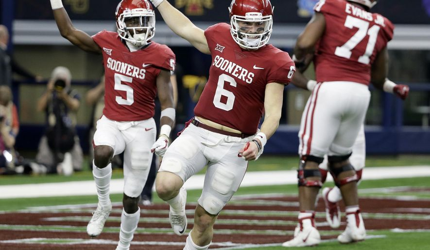 Oklahoma quarterback Baker Mayfield (6) and wide receiver Marquise Brown (5) celebrate hooking up for a long pass and touchdown score in the second half of the Big 12 Conference championship NCAA college football game against TCU on Saturday, Dec. 2, 2017, in Arlington, Texas. (AP Photo/Tony Gutierrez)