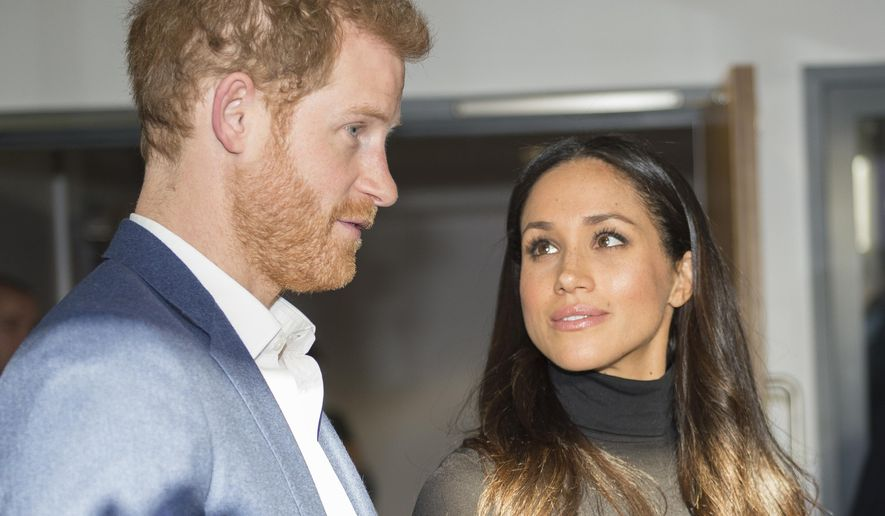 Britain's Prince Harry and his fiancee Meghan Markle speak with teachers at the Nottingham Academy in Nottingham, England, Friday, Dec. 1, 2017. It was announced on Monday that Prince Harry and American actress Meghan Markle are engaged and will marry in the spring of 2018. (Andy Stenning/Pool Photo via AP)