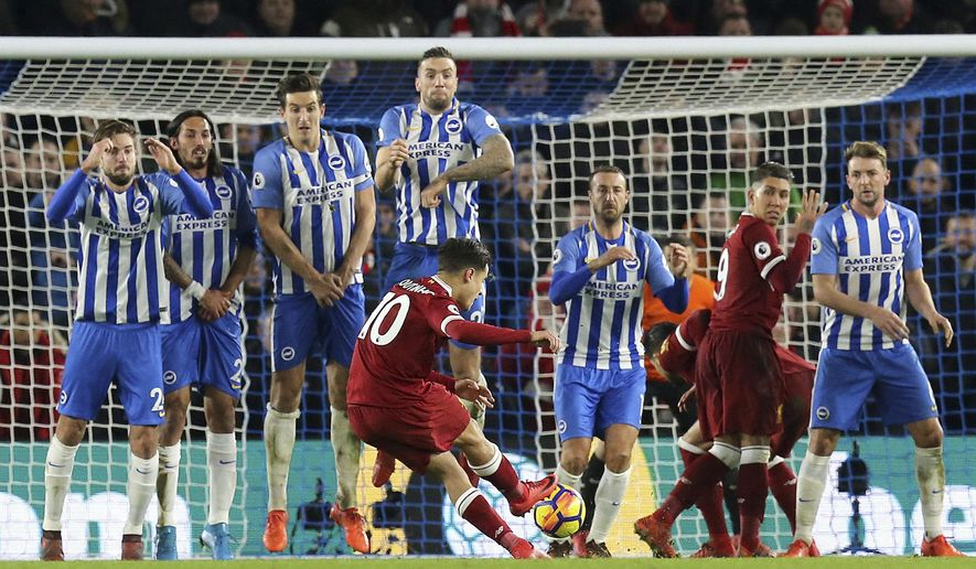 Liverpool's Philippe Coutinho scores his side's fourth goal during the English Premier League soccer match between Brighton & Hove Albion and Liverpool FC at the AMEX stadium, Brighton, England. Saturday. Dec. 2, 2017. (Gareth Fuller/PA via AP)