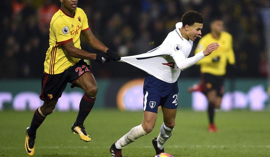 Watford's Marvin Zeegelaar grabs the t-shirt of Tottenham Hotspur's Dele Alli during the English Premier League soccer match at Vicarage Road, Watford, England, Saturday, Dec. 2, 2017. (Daniel Hambury/PA via AP)