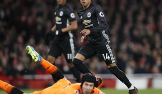 Manchester United's Jesse Lingard, right, celebrates after scoring his side's second goal past Arsenal goalkeeper Petr Cech, on the ground,during the English Premier League soccer match between Arsenal and Manchester United at the Emirates stadium in London, Saturday, Dec. 2, 2017. (AP Photo/Kirsty Wigglesworth)