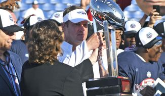 Florida Atlantic head coach Lane Kiffin prepares to hand the Conference USA trophy to his players after defeated North Texas in the championship NCAA college football game, Saturday, Dec. 2, 2017, in Boca Raton, Fla. (Jim Rassol/South Florida Sun-Sentinel via AP)