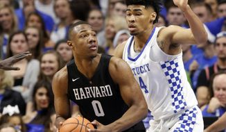 Harvard's Chris Lewis (0) looks for an opening on Kentucky's Nick Richards (4) during the first half of an NCAA college basketball game, Saturday, Dec. 2, 2017, in Lexington, Ky. (AP Photo/James Crisp)