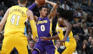 Los Angeles Lakers forward Kyle Kuzma, center, is trapped with the ball by Denver Nuggets forwards Juan Hernangomez, left, of Spain, and Kenneth Faried in the first half of an NBA basketball game Saturday, Dec. 2, 2017, in Denver. (AP Photo/David Zalubowski)