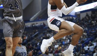 Connecticut's Jalen Adams shoots during an NCAA college basketball game against Monmouth Saturday, Dec. 2, 2017, at the XL Center in Hartford, Conn. (AP Photo/Stephen Dunn)