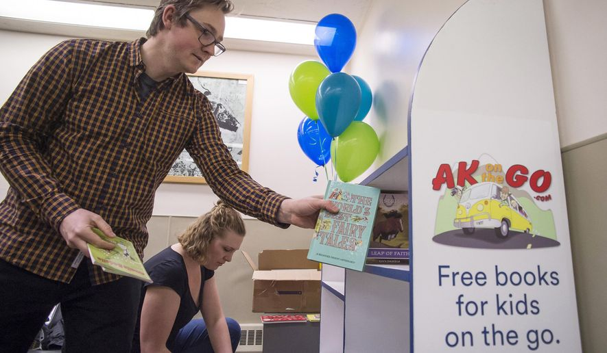 """University of Alaska Southeast Public Services Librarian Jonas Lamb, left, and Hannah Weed, of the Association for the Education of Young Children, stock a new bookshelf with children's books at the Juneau International Airport in Juneau, Alaska, on Wednesday, Nov. 15, 2017. A partnership between United Way, AEYC, Friends of The Juneau Public Libraries, Alaska Airlines and the Juneau Airport, the """"Read on the Fly"""" program will offer free books to children to take as they travel to or from Juneau.. (Michael Penn/Capitol City Weekly via AP)"""