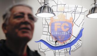 In this Wednesday, Nov. 29, 2017 photo, Carlos Martino, of Mariemont, left, is interviewed at the FC Cincinnati Team Store as an emblem depicting downtown Cincinnati and the Ohio River hangs on the wall behind the checkout counter in Cincinnati. While Ohio's capital city is trying to figure out how to keep its Major League Soccer franchise, the Columbus Crew, from moving to Austin, Texas, folks in Cincinnati are working on getting one, by getting an expansion promotion for the FC Cincinnati team. (AP Photo/John Minchillo)