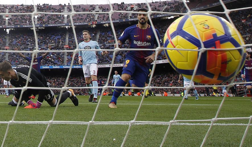 FC Barcelona's Luis Suarez, center right, scores during a Spanish La Liga soccer match between FC Barcelona and Celta Vigo at the Camp Nou stadium in Barcelona, Saturday, Dec. 2, 2017. (AP Photo/Manu Fernandez)