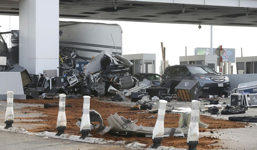 Debris is spread across several westbound lanes at the Bay Bridge toll plaza after a truck rammed through a toll booth, killing the toll collector inside, before daybreak in Oakland, Calif. on Saturday, Dec. 2, 2017. The two occupants of the truck were reportedly ejected from the vehicle. (Paul Chinn/San Francisco Chronicle via AP)
