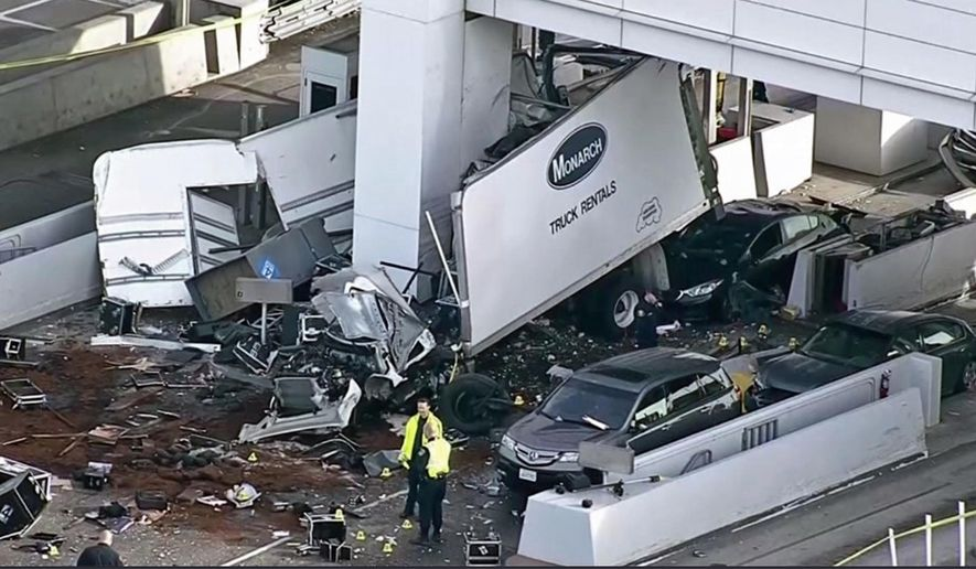 This still frame from video provided by KPIX-TV shows a large box truck that crashed into a toll booth on the San Francisco-Oakland Bay Bridge in Oakland, Calif., Saturday, Dec. 2, 2017. California Highway Patrol Officer Vu Williams said the box truck struck several vehicles and then hit a toll both, killing the attendant inside. The truck driver and a passenger were ejected from the vehicle, suffering serious injuries. (KPIX-TV via AP)