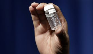 In this June 6, 2017, file photo, a reporter holds up an example of the amount of fentanyl that can be deadly, after a news conference about deaths from fentanyl exposure, at DEA Headquarters in Arlington, Va. The chief justice of the Massachusetts Trial Court told prosecutors she fears that allowing fentanyl and carfentanil into courtrooms as evidence puts people at risk even when the drugs are properly packaged. Some medical experts said a proposal to ban them from courtrooms appears to be driven by a misguided understanding of the real dangers of the substances. (AP Photo/Jacquelyn Martin, File)