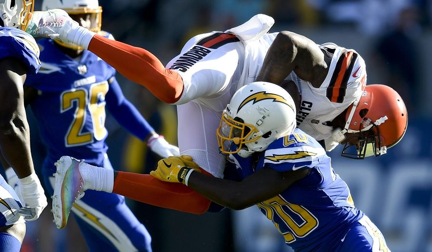 Cleveland Browns wide receiver Josh Gordon, top, is tackled by Los Angeles Chargers defensive back Desmond King during the first half of an NFL football game Sunday, Dec. 3, 2017, in Carson, Calif. (AP Photo/Kelvin Kuo)
