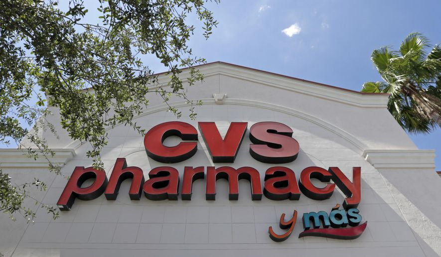 FILE - This May 15, 2017, file photo, shows a CVS pharmacy sign at a store in Hialeah, Fla. CVS will buy insurance giant Aetna in a roughly $69 billion deal that will help the drugstore chain provide more health care and keep a key client, according to a person with knowledge of the matter. (AP Photo/Alan Diaz, File)