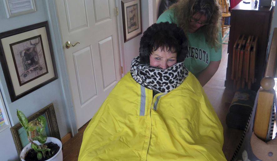 In a  Nov. 13, 2017 photo, Shannon Patterson helps Myrna Peterson get bundled up before her wheelchair commute to a community forum on driverless vehicles in Grand Rapids, Minn. A University of Minnesota transportation researcher says rural Minnesota residents could benefit from driverless cars. (Dan Kraker/Minnesota Public Radio via AP)