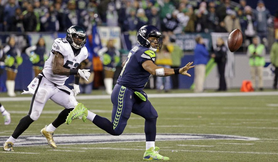 Seattle Seahawks quarterback Russell Wilson, right, shovels the ball on the run as Philadelphia Eagles' Nigel Bradham moves in during the second half of an NFL football game Sunday, Dec. 3, 2017, in Seattle. (AP Photo/Ted S. Warren)