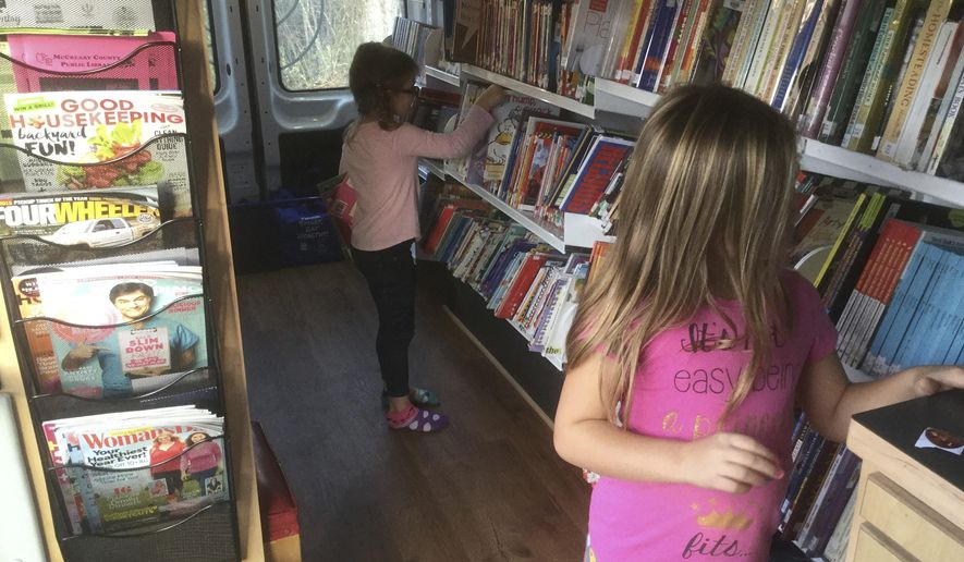 In this Nov. 21, 2017 photo, Kaylee Lay, 5, at rear, and her sister Kinley Lay, 6, get books from the bookmobile which came to their home in rural McCreary County, Ky. (Bill Estep /Lexington Herald-Leader via AP)