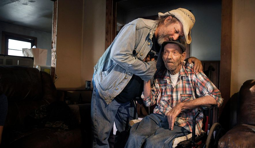 In this Saturday, Nov. 4, 2017 photo, Jack Stoddart embraces Willie Ray Abston, 78, who everyone knows as Cotton, in Crawford, Tenn. Abston has been in hospice three times, but continues to persevere. Stoddart, a man more well known as Hippie Jack, volunteers to delivered food to Abston. Stoddart has his mobile pantry outreach program that takes food and clothing to the needy in the ex-coal mining communities of Wilder, Cravenstown, and Vine Ridge. (Shelley Mays /The Tennessean via AP)