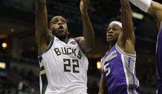 Milwaukee Bucks' Khris Middleton(22) drives against Sacramento Kings' De'Aaron Fox during the second half of an NBA basketball game Saturday, Dec. 2, 2017, in Milwaukee. (AP Photo/Jeffrey Phelps)