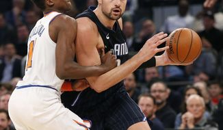 New York Knicks guard Frank Ntilikina (11) applies pressure to Orlando Magic center Nikola Vucevic (9) during the first half of an NBA basketball game in New York, Sunday, Dec. 3, 2017. (AP Photo/Kathy Willens)