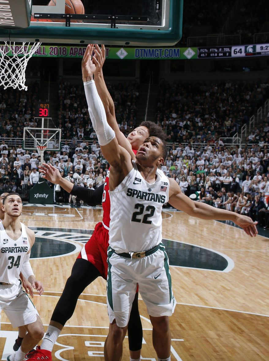 Michigan State's Miles Bridges (22) and Nebraska's Isaiah Roby reach for a rebound during the second half of an NCAA college basketball game, Sunday, Dec. 3, 2017, in East Lansing, Mich. Michigan State won 86-57. (AP Photo/Al Goldis)
