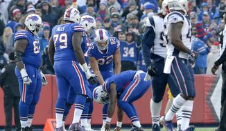 Buffalo Bills quarterback Tyrod Taylor, center, is slow to get up after a play against the New England Patriots during the second half of an NFL football game, Sunday, Dec. 3, 2017, in Orchard Park, N.Y. (AP Photo/Adrian Kraus)