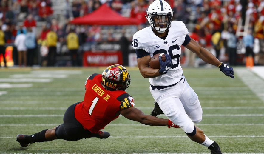 Penn State running back Saquon Barkley, right, rushes past Maryland linebacker Jermaine Carter Jr. in the first half of an NCAA college football game in College Park, Md., Saturday, Nov. 25, 2017. (AP Photo/Patrick Semansky)