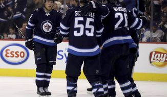 Winnipeg Jets' Patrik Laine (29) skates towards his teammates after scoring against the Ottawa Senators during the second period of an NHL hockey game in Winnipeg, Manitoba, Sunday, Dec. 3, 2017. (Trevor Hagan/The Canadian Press via AP)