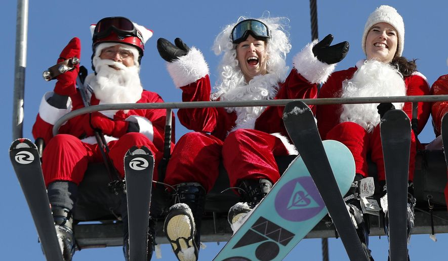 Skiers and a snowboarder dressed Santa Claus ride the chairlift at Sunday River during the ski resort's 18th annual Santa Sunday event, Sunday, Dec. 3, 2017, in Newry, Maine. In the name of charity, 160 skiing and snowboarding Santas raised $2,500 for the Sunday River Community Fund, a fund that benefits non-profits in area communities. (AP Photo/Robert F. Bukaty)