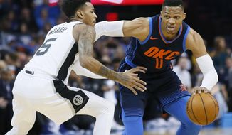 Oklahoma City Thunder guard Russell Westbrook (0) drives around San Antonio Spurs guard Dejounte Murray (5) during the first quarter of an NBA basketball game in Oklahoma City, Sunday, Dec. 3, 2017. (AP Photo/Sue Ogrocki)