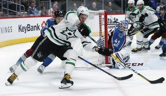 Dallas Stars right wing Alexander Radulov, front left, of Russia, wraps around the net for a shot as Colorado Avalanche defenseman Nikita Zadorov, of Russia, back left, pursues while goalie Jonathan Bernier blocks the net during the second period of an NHL hockey game Sunday, Dec. 3, 2017, in Denver. (AP Photo/David Zalubowski)