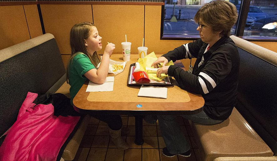 In this Nov. 7, 2017, photo, Kidney recipient Natasha Fuller of Oakfield eats in McDonalds with her grandma Chris Burleton. A tradition they keep after going to doctor visits for Natasha. More than a year after she received a life-saving kidney from a teacher at her Wisconsin schools, Fuller is an exuberant 9-year-old who can now enjoy the taste of chocolate. (Doug Raflik/The Reporter via AP)