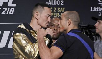In a Thursday, Nov. 30, 2017 photo,  Max Holloway, left, faces Jose Aldo during media day for the UFC 218 mixed martial arts fight in Detroit. Holloway respects Aldo, saying he's one of the greatest ever in mixed martial arts but is hoping to play a part in beginning to end Aldo's career. The Hawaiian fighter beat Aldo in his native Brazil in June, earning the featherweight title, and he is aiming to do it again in a rematch at UFC 218 on Saturday in Detroit. (AP Photo/Carlos Osorio)