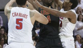 Southern California forward Chimezie Metu (4) is tied up by SMU defenders Ethan Chargois (5) and Jimmy Whitt (31) during the first half of an NCAA college basketball game in Dallas, Saturday, Dec. 2, 2017. (AP Photo/LM Otero)