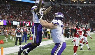 Minnesota Vikings running back Jerick McKinnon celebrates his touchdown with Jeremiah Sirles, right, during the second quarter against the Atlanta Falcons in an NFL football game Sunday, Dec. 3, 2017, in Atlanta. The Vikings won 14-9. (Curtis Compton/Atlanta Journal-Constitution via AP)