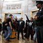 """With shirts saying """"fight poverty not the poor,"""" people with the """"Poor People's Campaign"""" gesture the group to remain quiet as the group leaves the Capitol Rotunda after praying in an act of civil disobedience in protest of the Republican tax overhaul on Monday. (Associated Press)"""