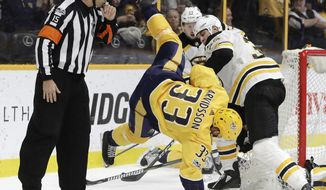 Nashville Predators left wing Viktor Arvidsson (33), of Sweden, takes a fall after colliding with Boston Bruins defenseman Zdeno Chara, right, of Slovakia, in the second period of an NHL hockey game Monday, Dec. 4, 2017, in Nashville, Tenn. (AP Photo/Mark Humphrey)