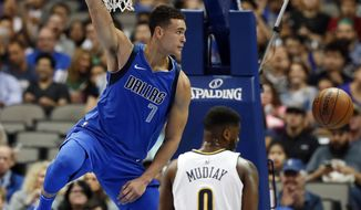 Dallas Mavericks forward Dwight Powell (7) hangs from the rim after dunking over Denver Nuggets guard Emmanuel Mudiay (0) in the first half of an NBA basketball game, Monday, Dec. 4, 2017, in Dallas. (AP Photo/Tony Gutierrez)