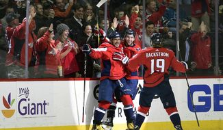 Washington Capitals left wing Alex Ovechkin, front left, of Russia, celebrates his goal with Tom Wilson, center, and Nicklas Backstrom (19), of Sweden, during the second period of an NHL hockey game against the San Jose Sharks, Monday, Dec. 4, 2017, in Washington. (AP Photo/Nick Wass)