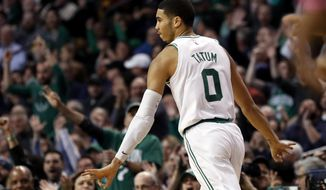 Boston Celtics' Jayson Tatum signals after making a three point basket against the Milwaukee Bucks during the first quarter of an NBA basketball game in Boston, Monday, Dec. 4, 2017. (AP Photo/Winslow Townson)