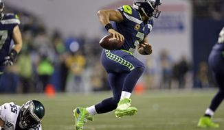 Seattle Seahawks quarterback Russell Wilson, right, leaps away from Philadelphia Eagles defender Brandon Graham in the second half of an NFL football game Sunday, Dec. 3, 2017, in Seattle. The Seahawks won 24-10. (AP Photo/John Froschauer)
