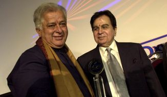 FILE- In this June 2, 2005 file photo, legendary Bollywood actor Dilip Kumar, right, looks at veteran actor Shashi Kapoor, left, at the inauguration of a new cinema in Mumbai, India. Kapoor was felicitated at the event. Kapoor, a prolific Bollywood actor and producer from the 1970s and '80s, died Monday, Dec. 4, 2017 after a long illness. He was 79. (AP Photo/Aijaz Rahi, File)