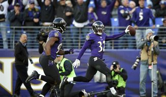 Baltimore Ravens free safety Eric Weddle (32) runs an intercepted pass back for a touchdown alongside teammate Matt Judon in the second half of an NFL football game against the Detroit Lions, Sunday, Dec. 3, 2017, in Baltimore. (AP Photo/Nick Wass)