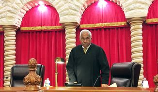 Nevada Supreme Court Justice Michael Douglas prepares to take his seat for oral arguments in an appellate case Monday, Dec. 4, 2017, in Las Vegas. Douglas became the first black justice on the court when he was appointed in March 2004. He announced he plans to retire after his term expires at the end of 2018. (AP Photo/Ken Ritter)